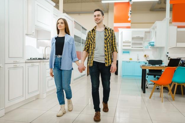 Jong liefdepaar in de showroom van de meubelwinkel.