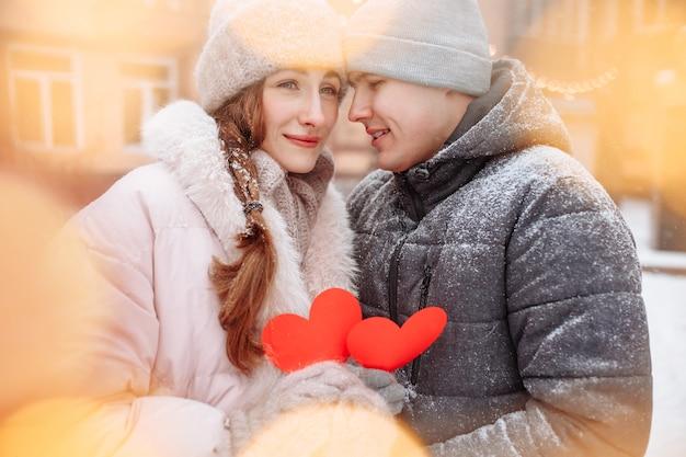 Jong liefdevol paar buiten op een winterse dag met rode papieren harten in hun handen die vreugde en liefde voelen. romantische man en vrouw vieren valentijnsdag onder de sneeuw in een park.