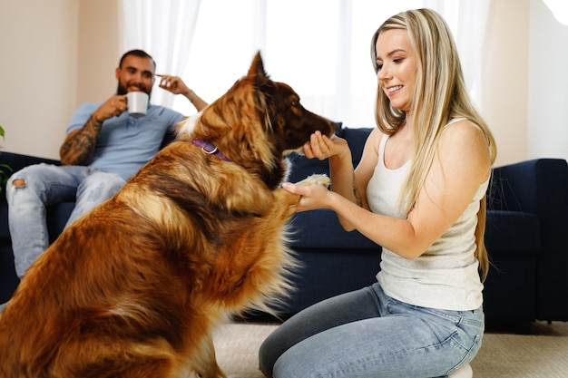 Jong liefdevol paar ontspannen in de woonkamer met hun hond huisdier