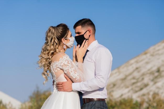 Jong liefdevol paar wandelen in medische maskers in het park tijdens hun trouwdag.