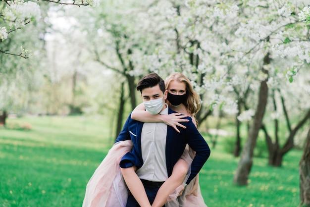 Jong liefdevol paar wandelen in medische maskers in het park tijdens quarantaine op hun trouwdag.