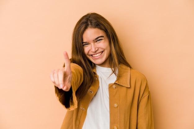 Jong mager kaukasisch tienermeisje die nummer één met vinger tonen.