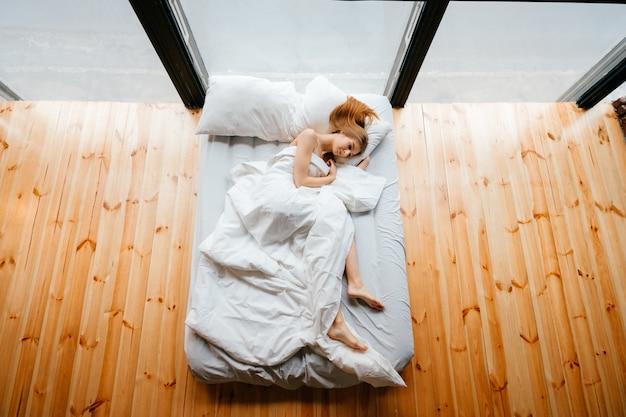 Jong mager mooi blootvoets meisje die in wit bed met deken en hoofdkussens liggen en slapen. ochtend ontspannen op de bank. gembervrouw die in studioappartement rusten met houten vloer en reusachtige vensters