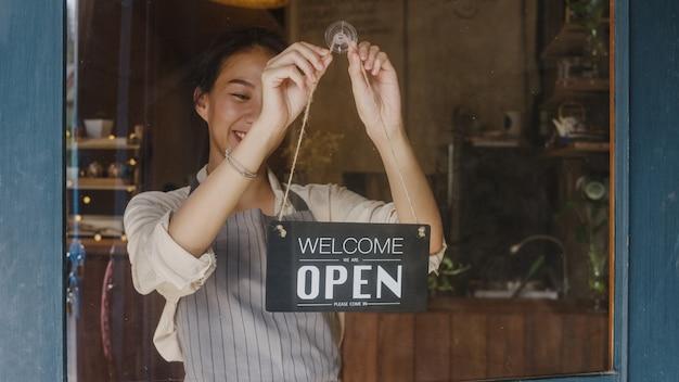 Jong managermeisje verandert een bord van gesloten naar open bord op deurcafé dat naar buiten kijkt en wacht op klanten na afsluiting.