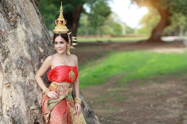 Jong manier aziatisch meisje in thais traditioneel kostuum die zich met grote groene bomen bevinden