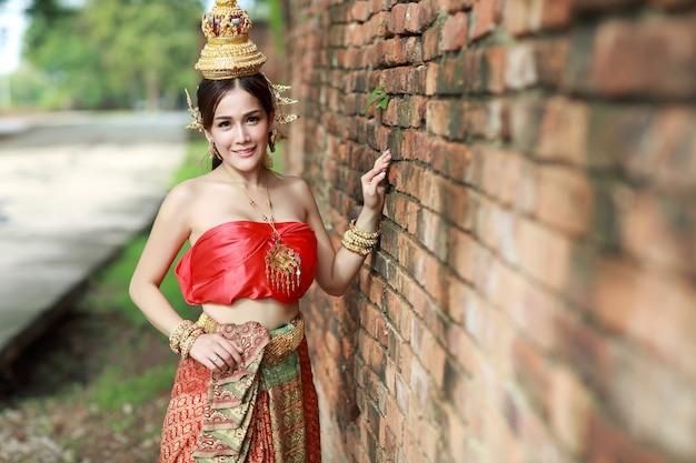 Jong manier aziatisch meisje in thais traditioneel kostuum die zich met oude bakstenen muur bevinden