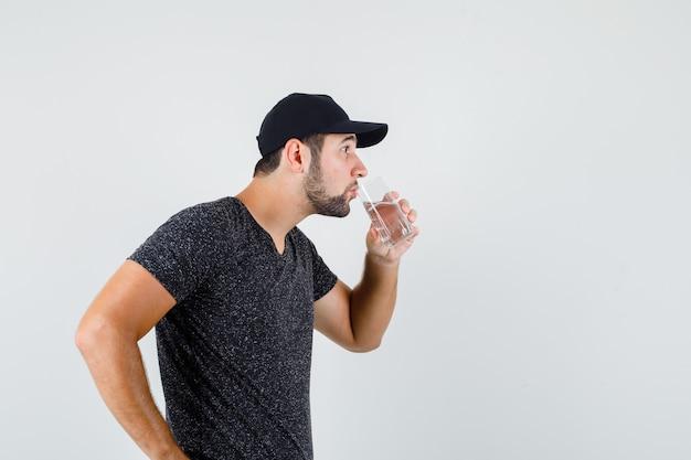 Jong mannelijk drinkwater in t-shirt en pet en dorstig op zoek