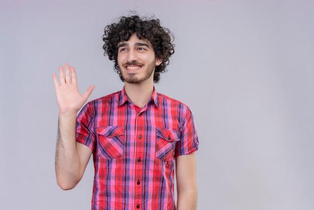 Jong mannelijk krullend haar geïsoleerd kleurrijk overhemd hand omhoog belofte gebaar