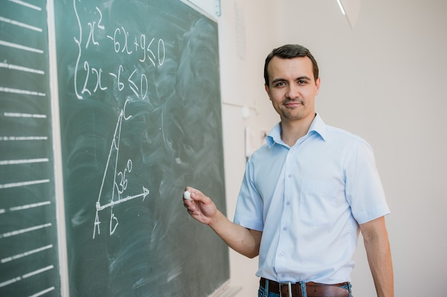 Jong mannelijk leraar of studentenholdingskrijt die op bord in klaslokaal schrijven