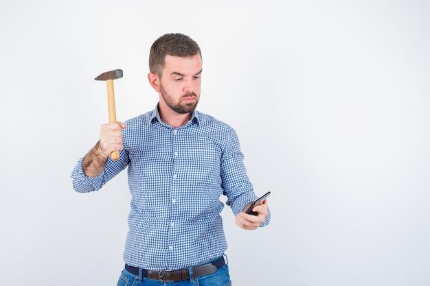 Jong mannetje dat beweert mobiele telefoon te slaan met een hamer in overhemd, spijkerbroek en ernstig, vooraanzicht kijkt.