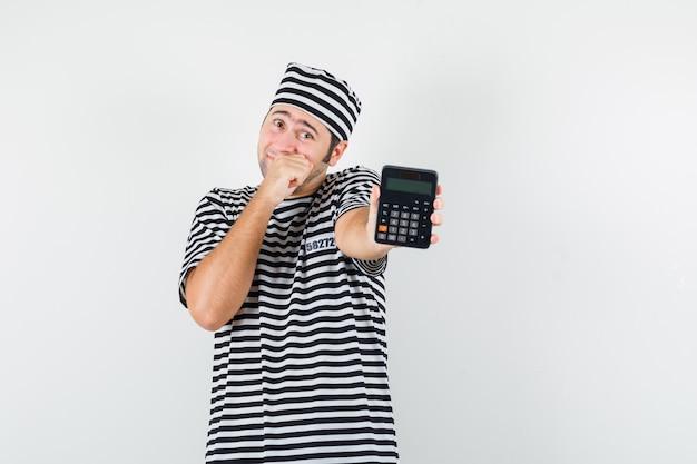 Jong mannetje dat calculator in t-shirt, hoed toont en beschaamd kijkt. vooraanzicht.