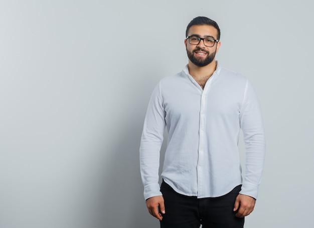 Jong mannetje dat camera in overhemd, broek bekijkt en zelfverzekerd kijkt