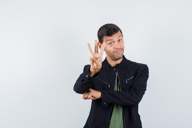 Jong mannetje dat drie vingers in t-shirt, jasje steunt en vrolijk, vooraanzicht kijkt.