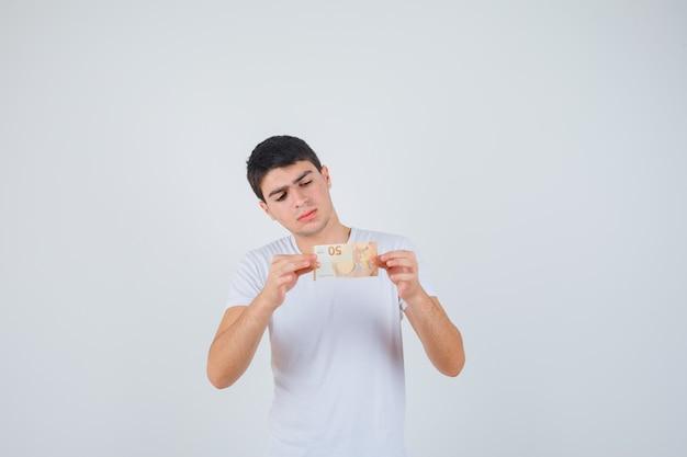 Jong mannetje dat eurobankbiljet in t-shirt toont en voorzichtig, vooraanzicht kijkt.