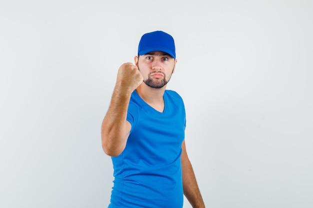 Jong mannetje dat gebalde vuist toont om in blauw t-shirt en pet te bedreigen en woedend kijkt