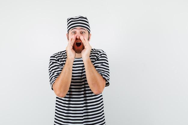 Jong mannetje dat geheim vertelt of iets in t-shirt, hoed aankondigt en blij, vooraanzicht kijkt.