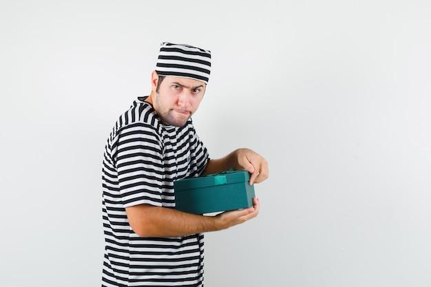 Jong mannetje dat giftdoos in t-shirt, hoed probeert te openen en nieuwsgierig, vooraanzicht kijkt.