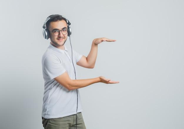Jong mannetje dat grootteteken in wit t-shirt, broek toont en zelfverzekerd kijkt