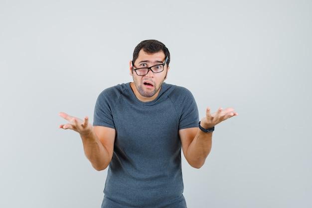 Jong mannetje dat hulpeloos gebaar in grijs t-shirt toont en verward kijkt