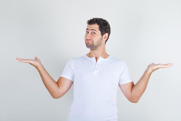 Jong mannetje dat hulpeloos gebaar in wit t-shirt toont en verward kijkt