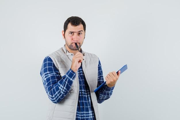 Jong mannetje dat iets denkt om in overhemd, jasje te schrijven en zorgvuldig, vooraanzicht kijkt.