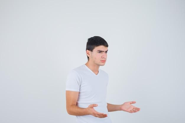 Jong mannetje dat iets in t-shirt beweert te tonen of vast te houden en ernstig kijkt. vooraanzicht.
