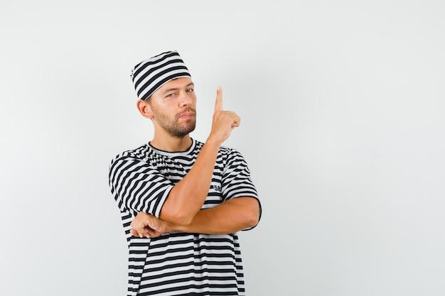 Jong mannetje dat in gestreepte t-shirthoed benadrukt en zelfverzekerd kijkt