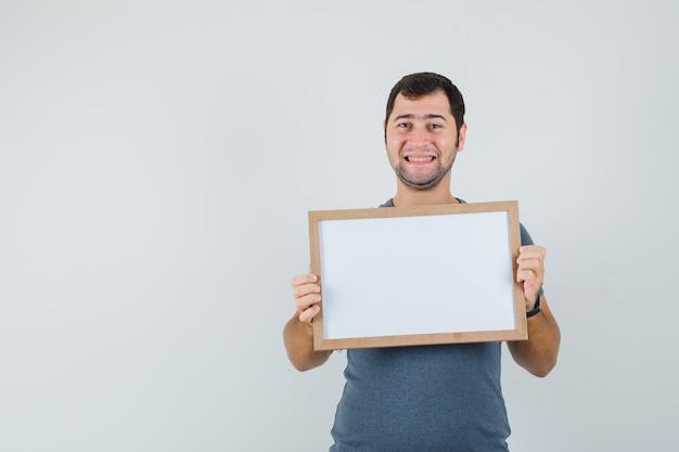 Jong mannetje dat in grijs t-shirt leeg frame houdt en vrolijk kijkt