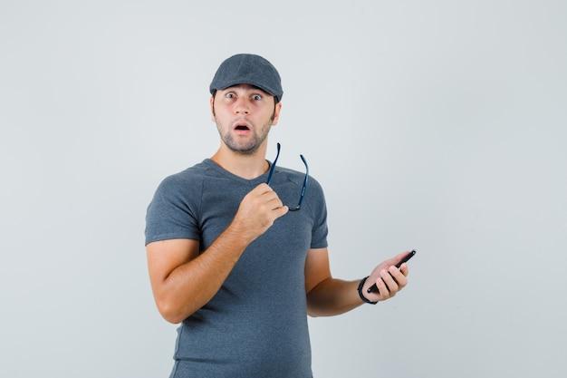 Jong mannetje dat in grijs t-shirtglb mobiele telefoon en glazen houdt en verrast kijkt