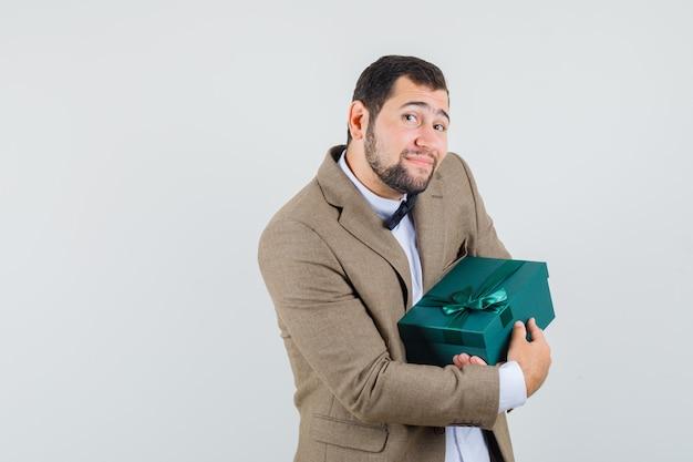 Jong mannetje dat in kostuum huidige doos houdt en vreugdevol, vooraanzicht kijkt.