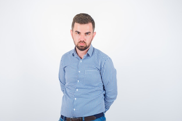 Jong mannetje dat in overhemd camera bekijkt en ernstig, vooraanzicht kijkt.