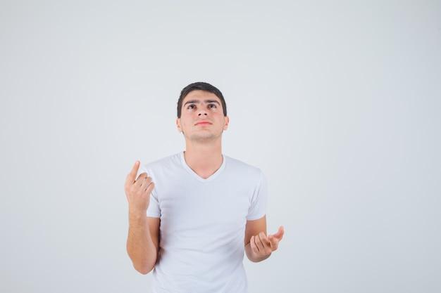 Jong mannetje dat in t-shirt benadrukt en peinzend, vooraanzicht kijkt.
