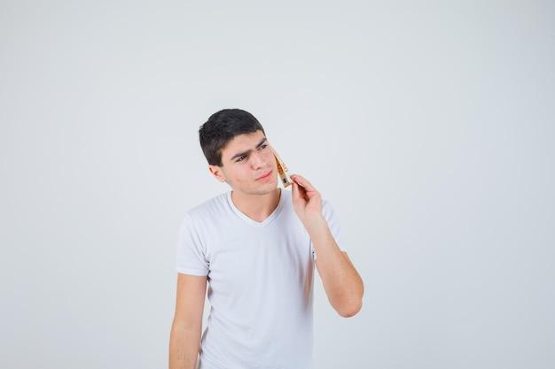 Jong mannetje dat in t-shirt eurobankbiljet op wang houdt en nadenkend, vooraanzicht kijkt.