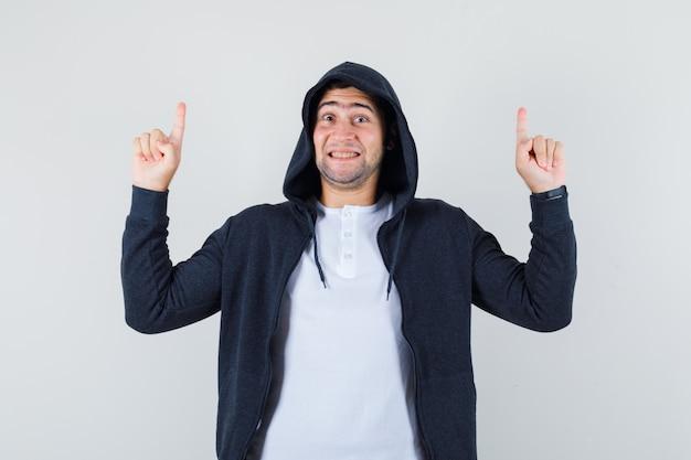 Jong mannetje dat in t-shirt, jasje benadrukt en vrolijk, vooraanzicht kijkt.