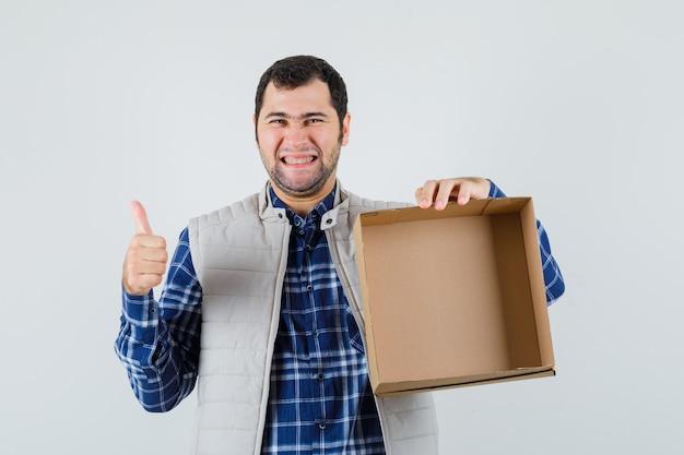 Jong mannetje dat lege doos toont terwijl het tonen van duim in overhemd, jasje en positief kijkt. vooraanzicht.