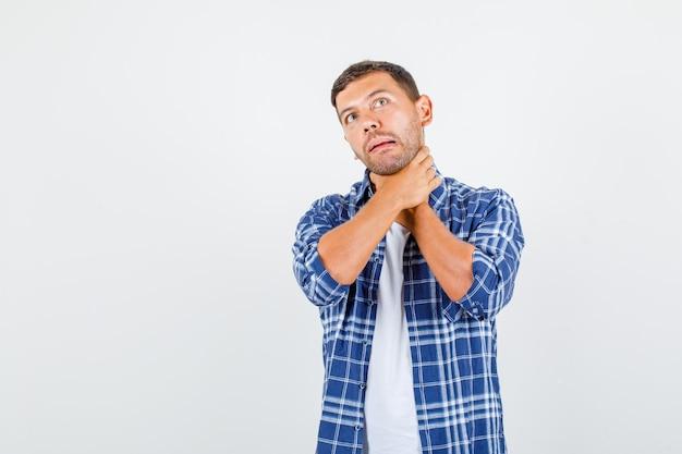Jong mannetje dat met handen op hals in overhemd verstikt en pijnlijk, vooraanzicht kijkt.