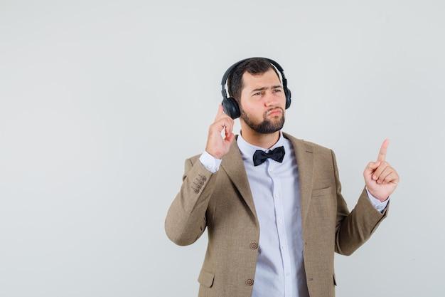 Jong mannetje dat met hoofdtelefoons luistert en in kostuum vooraanzicht benadrukt.