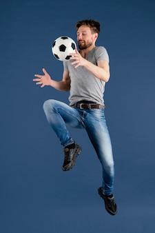 Jong mannetje dat met voetbalbal springt
