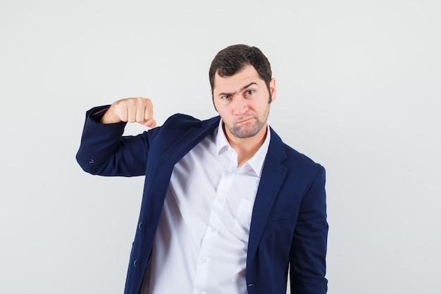 Jong mannetje dat met vuist in overhemd bedreigt