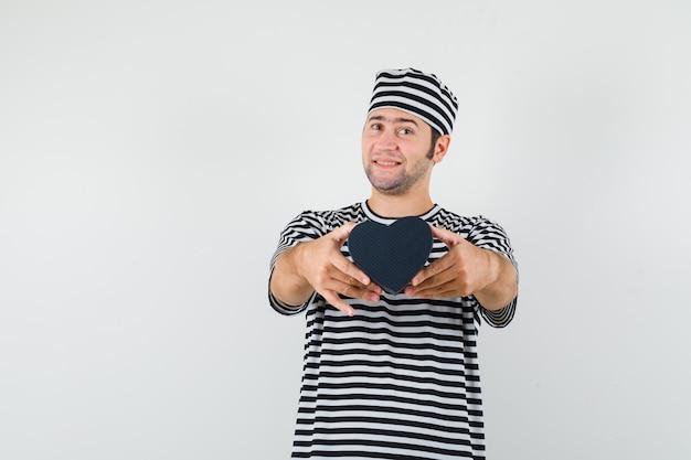 Jong mannetje dat minigiftdoos in gestreept t-shirt, glb toont en blij kijkt. vooraanzicht. ruimte voor tekst
