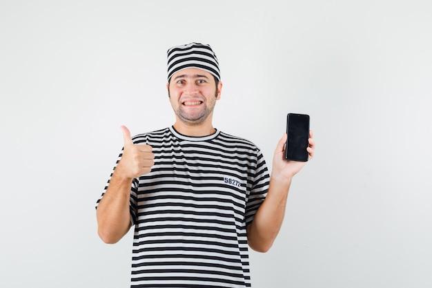 Jong mannetje dat mobiele telefoon houdt, duim in t-shirt, hoed toont en vreugdevol kijkt. vooraanzicht.