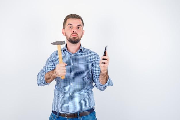 Jong mannetje dat mobiele telefoon houdt terwijl het houden van hamer in overhemd, jeans en ernstig kijkt. vooraanzicht.