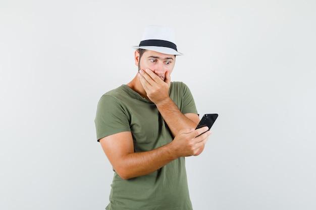 Jong mannetje dat mobiele telefoon in groen t-shirt en hoed bekijkt en verbaasd kijkt