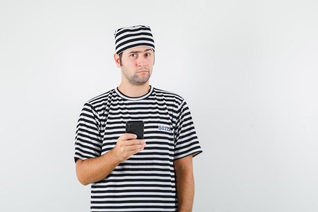 Jong mannetje dat mobiele telefoon in t-shirt, hoed houdt en aarzelend kijkt. vooraanzicht.