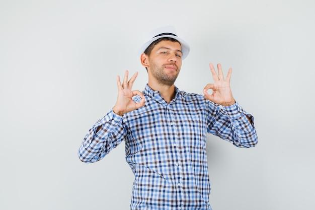 Jong mannetje dat ok gebaar in gecontroleerd overhemd, hoed toont en blij kijkt