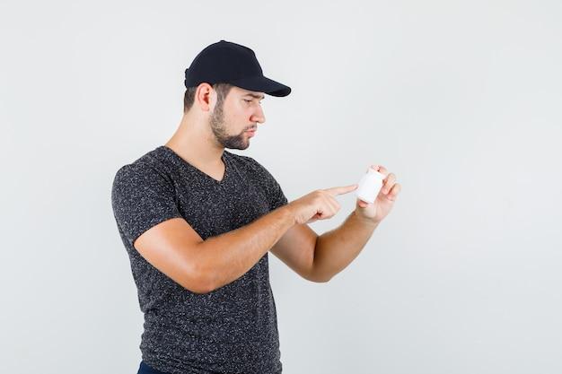 Jong mannetje dat op info over fles pillen in t-shirt en glb richt en voorzichtig kijkt