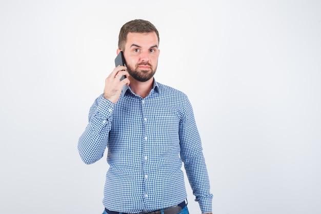 Jong mannetje dat op mobiele telefoon in overhemd, spijkerbroek spreekt en zelfverzekerd, vooraanzicht kijkt.