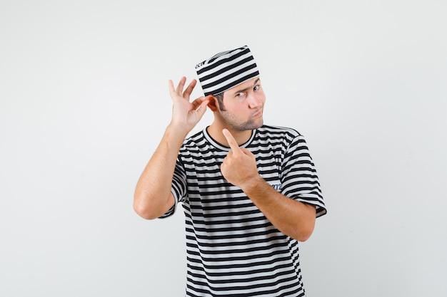 Jong mannetje dat op zijn oor in t-shirt, hoed richt en peinzend kijkt. vooraanzicht.