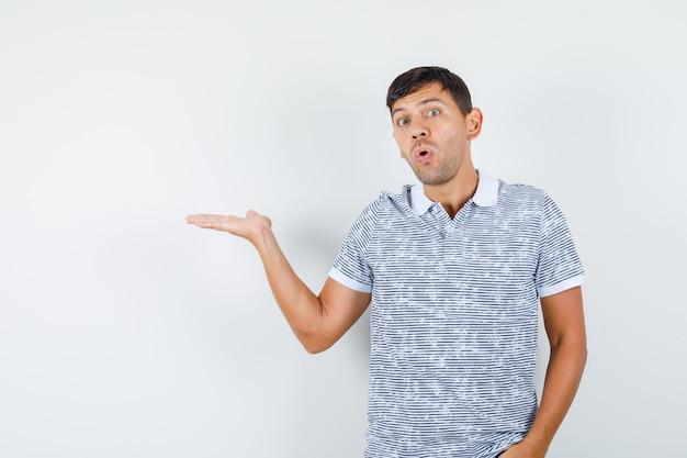 Jong mannetje dat palm opzij in t-shirt uitspreidt en verbaasd kijkt