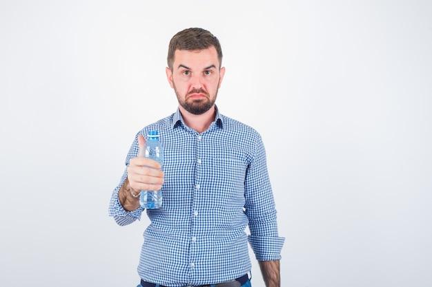 Jong mannetje dat plastic waterfles in overhemd, jeans houdt en ernstig kijkt. vooraanzicht.